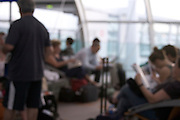 out of focus view of tourists waiting at an airport terminal