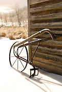 Wooden plow against barn in snow