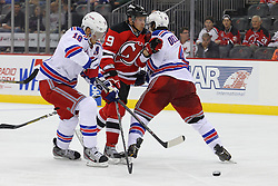 Sep 16, 2013; Newark, NJ, USA; New Jersey Devils left wing Mattias Tedenby (9) is hit by New York Rangers defenseman Michael Del Zotto (4) and New York Rangers defenseman Marc Staal (18) during the second period at Prudential Center.