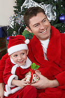 Man with arm around boy (5-6) in Santa hat holding Christmas present
