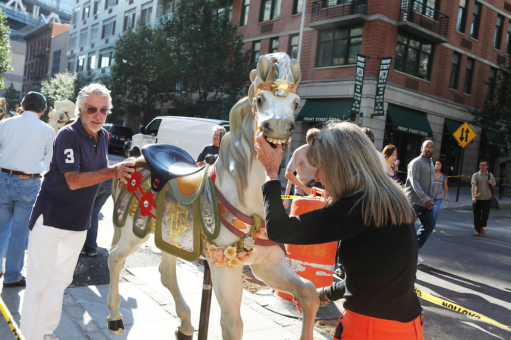Jane and David Walentas guide a carousel horse from her studio to Brooklyn Bridge Park on September 2.  Jane's Carousel is the work of Mrs. Walentas, who donated the piece to the park after years of restoring the carousel to its original splendor. ..CREDIT: Daniella Zalcman for The Wall Street Journal.SLUG: NYJANES