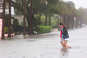 Residents walk across the flooded historic Battery area as Hurricane Joaquin brings heavy rain, flooding and strong winds as it passes offshore October 3, 2015 in Charleston, South Carolina.
