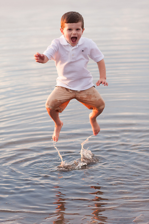 Young boy leaping in the water of Cape Cod bay in Brewster