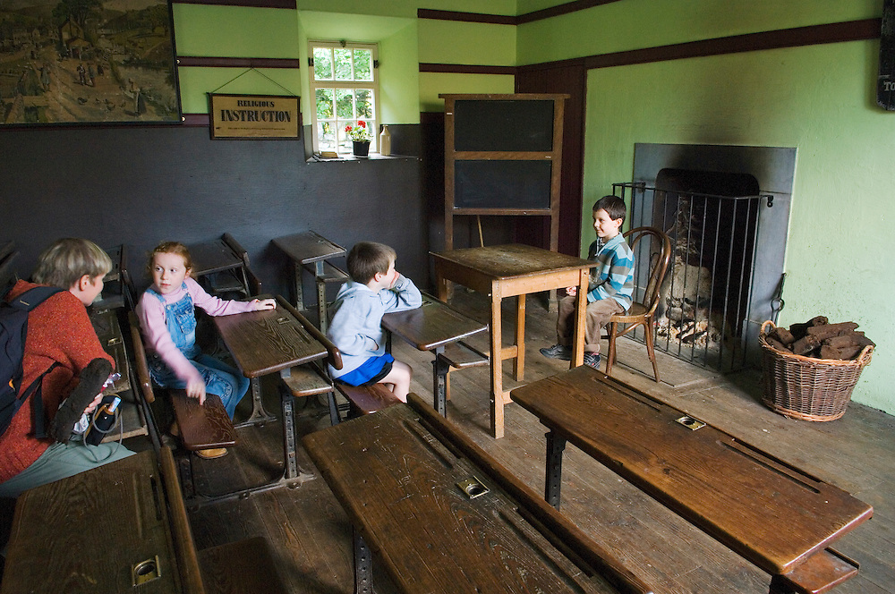 Bunratty Folk Park, Bunratty Castle, Co. Clare, Ireland. Children pupils and mother teacher explore the School House classroom.