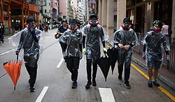 Hong Kong. 6 October 2019. Tens of thousands of pro-democracy protestors march in pouring rain through centre of Hong Kong today from Causeway Bay to Central. Peaceful march later turned violent as a hard-core of protestors confronted police. Pic; protestors retreat through Wanchai. Iain Masterton/Alamy Live News.