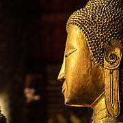 The profile of a Buddha statue at Wat Mai Suwannaphumaham.  Wat Mai, as it is often known, is a Buddhist temple in Luang Prabang, Laos, located near the Royal Palace Museum. It was built in the 18th century and is one of the most richly decorated Wats in Luang Prabang.