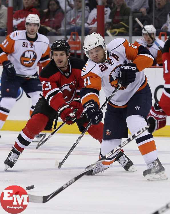 Apr 10, 2010; Newark, NJ, USA; New York Islanders right wing Kyle Okposo (21) makes a pass while being defended by New Jersey Devils right wing David Clarkson (23) during the second period at the Prudential Center.
