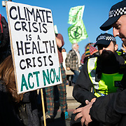 Thousands of Extinction Rebellion activists took over 5 bridges in Central London and blocked them for the day, November 17 2018, Central London, United Kingdom. Lambeth Bridge; police is talking to a female activists to convince her to get up not to get arrested. Around 11am people on all bridges sat down in the road and blocked traffic from coming through and stayed till late afternoon. The actvists believe that the government is not doing enough to avoid catastrophic climate change and they demand the government take radical action to save future generations and the planet. Many are willing to be arrested peacefully protesting and up to 80 were arrested on the day. Extinction Rebellion is a grass root climate change group started in 2018 and has gained a huge following of people commited to peaceful protests and who ready to be arrested. Their major concern is that the world is facing catastropohic climate change and they want the British government to act now to save future generations.