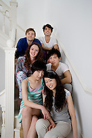 Group portrait of young friends sitting in stairway
