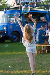 © Licensed to London News Pictures. 29/05/2016. Hay-on-Wye, Powys, Wales, UK. A young child chases bubbles from Dr Zigg's on the fourth day of the 'HowTheLightGetsIn' Festival of Ideas at Hay-on-Wye, Wales. Photo credit: Graham M. Lawrence/LNP