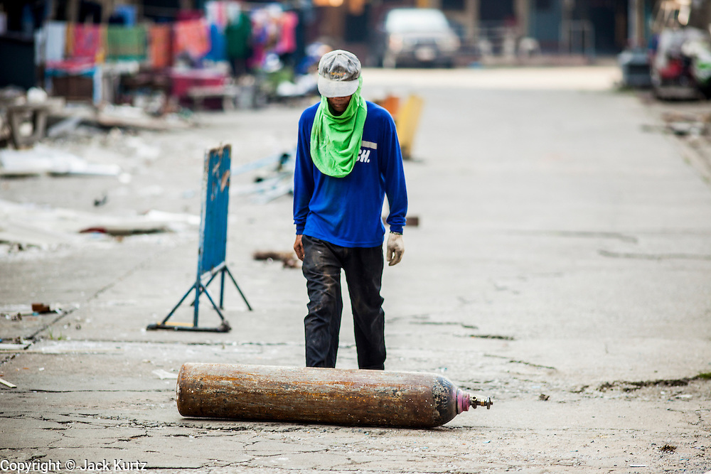 """03 DECEMBER 2012 - BANGKOK, THAILAND:    A worker rolls an oxygen tank down a deserted street in the """"Washington Square"""" district in Bangkok. Washington Square was a notorious adult """"entertainment"""" and red light district on Sukhumvit Soi 22 in Bangkok. Many of the bars and massage parlors catered in the district to older American and European men and opened in the 1960's when Bangkok was a """"R&R"""" destination for American servicemen in Vietnam. It's being torn down to make way for new high rise hotels and condominiums.       PHOTO BY JACK KURTZ"""