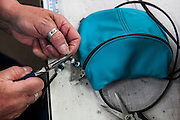 DEXTER, ME - AUGUST 4, 2015:  Cheryl Sullivan (59) an employee at Erda Handbags, adds beads to handbag straps at the company's production facility in Dexter, Maine. Since most of Erda's employees are 60 years or older they have implemented a flexible scheduling system and invested in more ergonomic machines to accommodate their aging workforce. <br /> Craig Dilger for The New York Times