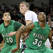 Tom Herzog (C) gets blocked out by Marshall forward Tirrell Baines (30) and Marshall guard/forward Dago Pena (10) during a Conference USA NCAA basketball game between the Marshall Thundering Herd and the Central Florida Knights at the UCF Arena on January 5, 2011 in Orlando, Florida. Central Florida won the game 65-58 and extended their record to 14-0.  (AP Photo/Alex Menendez)