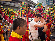 17 AUGUST 2013 - BANGKOK, THAILAND:    A man prays at Erawan Shrine in Bangkok while a dragon dance troupe performs around him. The Chinese Dragon Dance began during the Han Dynasty which lasted from 206 BC to 24 AD. In those ancient days it was performed by the people of China specifically to please their ancestors and to insure sufficient rain for a plentiful crop. In this way they hoped to protect against hunger and sickness. Over time the Dragon Dance became a central feature in Chinese celebrations with different colors symbolizing different characteristics or desired features; red for excitement, green for a good harvest, yellow for a solemn empire and gold or silver for prosperity. The Dragon Dance is a well-choreographed event whose difficulty is dependent upon the performers' skill. The length of the dragon indicates just how much luck it will bring in the coming year, but a longer dragon requires more performers with great skill as an error by one can ruin the entire performance. The dragon is typically between 82 and 229 feet long. The head along can weigh as much as 31 pounds. Both strength and skill are both required in performing the Chinese Dragon Dance.        PHOTO BY JACK KURTZ