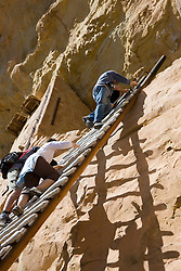 Park visitors climb a ladder to the entrance of Balcony House, Mesa Verde National Park, near Cortez, Colorado.
