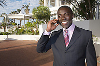 Businessman stands holding mobile phone in front of hotel