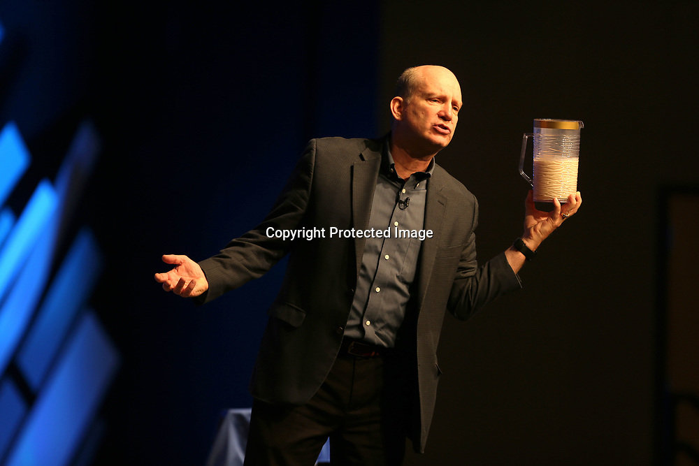 Billy Riggs holds up a pitchers as he asks teachers if they have a half full or half empty glass during his time as guest speaker at the Lee County Schools back-to-school convocation at The Orchard in Tupelo.