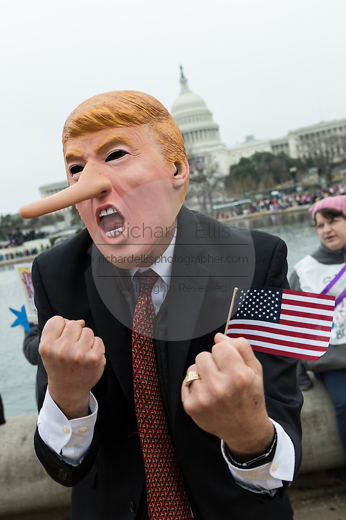 A demonstrator wearing a Donald Trump costume during the Women's March on Washington January 21, 2017 in Washington, DC. More than 500,000 people crammed the National Mall in a peaceful and festival rally in a rebuke of the new president.