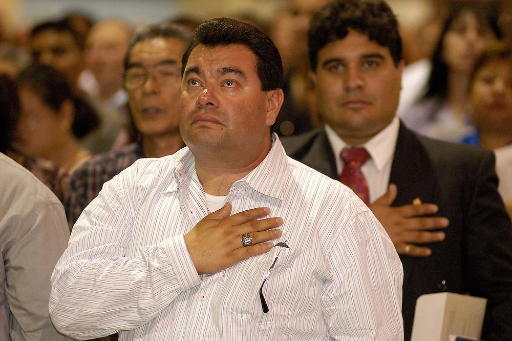 POMONA, CALIFORNIA  8/18/04--Originally from Mexico, a man places his hand over his heart as tears well up in his eyes during the singing of the national anthem at a citizenship ceremony in Pomona, California.<br />
