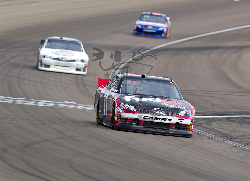 LAS VEGAS, NV - MAR 11, 2012:  Denny Hamlin (11) and Landon Cassill (83) battle for position during the Kobalt Tools 400 race at the Las Vegas Motor Speedway in Las Vegas, NV.