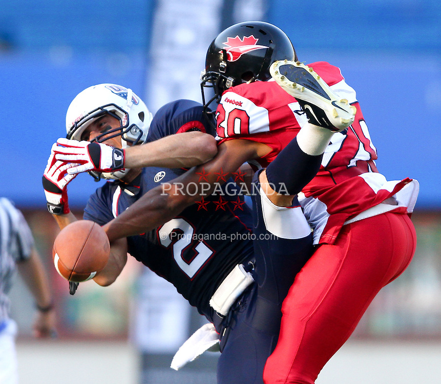 16.07.2011, Ernst Happel Stadion, Wien, AUT, American Football WM 2011, United States of America (USA) vs Canada (CAN), im Bild Ricardo Lenhart (USA, #2, WR) gets tackled by Sammy Okpro (Canada, #20, DB) while he tries to catch the ball // during the American Football World Championship 2011 game, USA vs Canada, at Ernst Happel Stadion, Wien, 2011-07-16, EXPA Pictures © 2011, PhotoCredit: EXPA/ T. Haumer