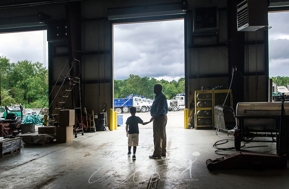 Pat Barber and his son, James Barber, are silhouetted as they leave the maintenance shop at Superior Transportation, Sept. 30, 2015, in North Charleston, South Carolina. Barber started the company in 1998. James, 6, is already showing a big interest in the company and its Mack trucks, and Barber says he hopes he will follow in his footsteps and carry on the family legacy.  (Photo by Carmen K. Sisson/Cloudybright)