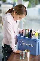 Girl (10-12) putting empty vessels into recycling container side view