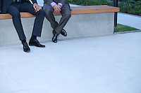 Businessmen sitting on wall