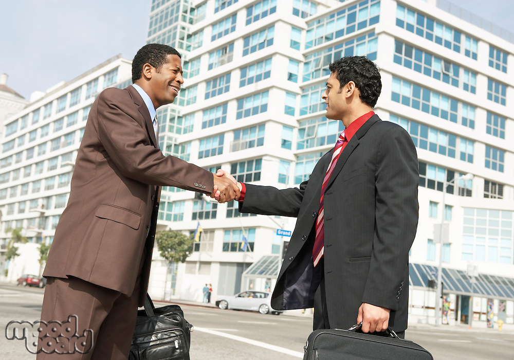 Two business men shaking hands on street