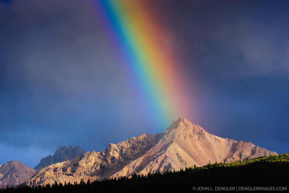 An evening rainbow basks upon an unnamed mountain of the Alaska Range located in the upper Teklanika River valley in Denali National Park and Preserve. The view is from the Igloo Creek Campground.