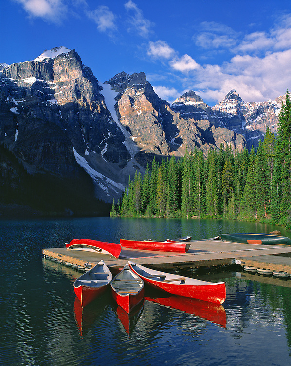 Bright red canoes contrast sharply with the deep blues and greens of Moraine Lake in the Valley of the Ten Peaks, in Alberta's Banff National Park. ©Ric Ergenbright