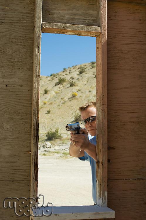 Man aiming hand gun at firing range