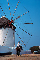 Greek man on horseback with windmill in background, Island of Mykonos, Greece