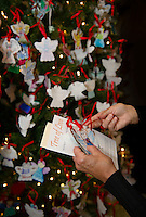 """Sue Vincent finds her loved ones """"angels"""" made by Gilford Elementary students to take home following the LRGH Auxiliary Tree of Love Services held Thursday afternoon in the LRGH Atrium.  (Karen Bobotas/for the Laconia Daily Sun)"""