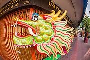 14 OCTOBER 2012 - BANGKOK, THAILAND:   A dragon used by performers in a procession in front of a closed shop on the first day of the Vegetarian Festival in Bangkok's Chinatown. The Vegetarian Festival is celebrated throughout Thailand. It is the Thai version of the The Nine Emperor Gods Festival, a nine-day Taoist celebration beginning on the eve of 9th lunar month of the Chinese calendar. During a period of nine days, those who are participating in the festival dress all in white and abstain from eating meat, poultry, seafood, and dairy products. Vendors and proprietors of restaurants indicate that vegetarian food is for sale by putting a yellow flag out with Thai characters for meatless written on it in red.     PHOTO BY JACK KURTZ
