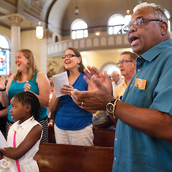 2 AUG. 2015 -- ST. LOUIS -- Jordyn Brownlee (left), 9, and August Lewis (right) join other worshipers during Mass Mob III at Sts. Teresa and Bridget Catholic Parish in St. Louis Sunday, Aug. 2, 2015. The event brings Catholics from across the Archdiocese of St. Louis to worship at historic, urban parishes.<br /> <br /> Photo by Sid Hastings.