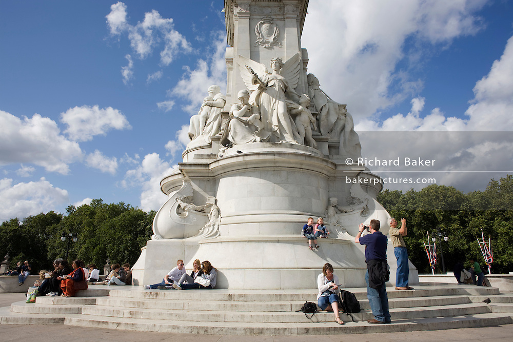 Tourists rest in late summer sunshine at the Grade 1 listed  Victoria Memorial sculpture opposite Buckingham Palace.