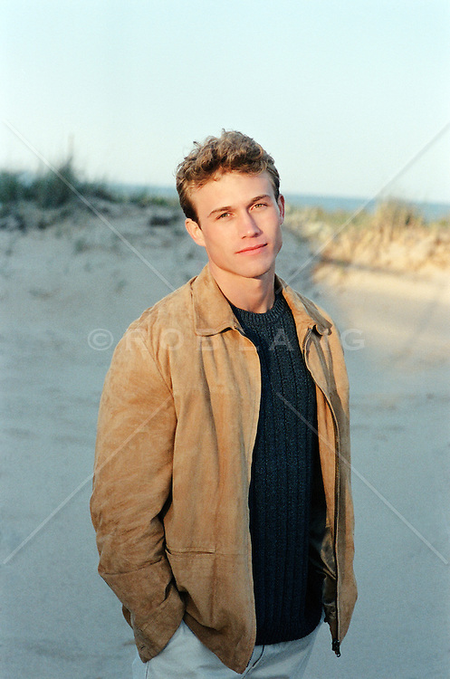 young man standing on the beach in sunlight