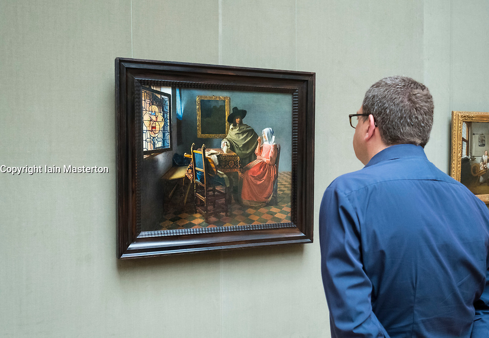 Man looking at painting by Johannes  Vermeer , The Glass of Wine ,at Gemaldegalerie museum, at Kulturforum in Berlin, Germany