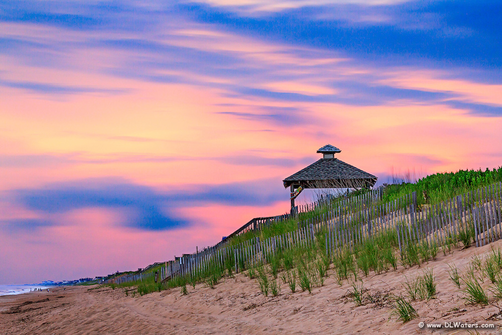 Sunrise clouds moving across the frame in a long exposure of a gazebo at the beach on the Outer Banks.