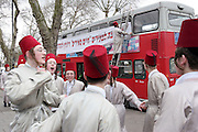 A group of Orthodox Jewish boys from the Viznitz Yeshiva (school) dressed in fancy dress sing and dance in the street. Other members of the group decorate the double-decker bus with banners that they will travel on for the Jewish festival of Purim. They will visit several local wealthy businessmen collecting money for their school.