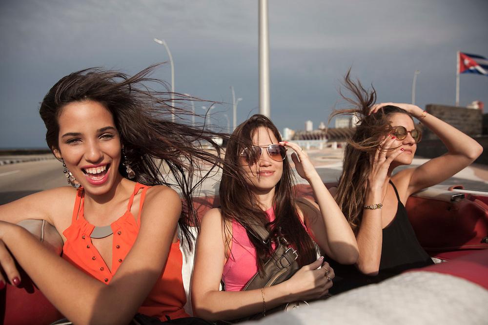 Young women enjoy a sunny afternoon during a ride in an old American convertible in Havana, Cuba.<br /> <br /> Dos j&oacute;venes cubanas y una turista disfrutan de una paseo al atardecer en uno de los tradicionales coches antiguos descapotables que circulan por La Habana.
