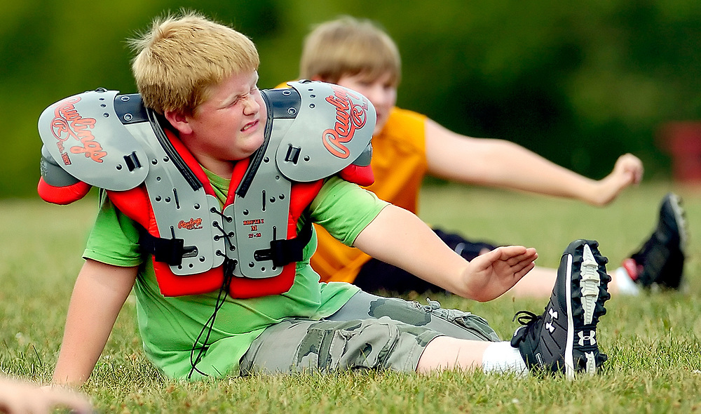 Joseph Walston, 10, strains to reach his toes while doing stretches during the first day of youth football practice at the Lutheran School Association field Monday, Aug. 6, 2007, in Decatur, Ill.
