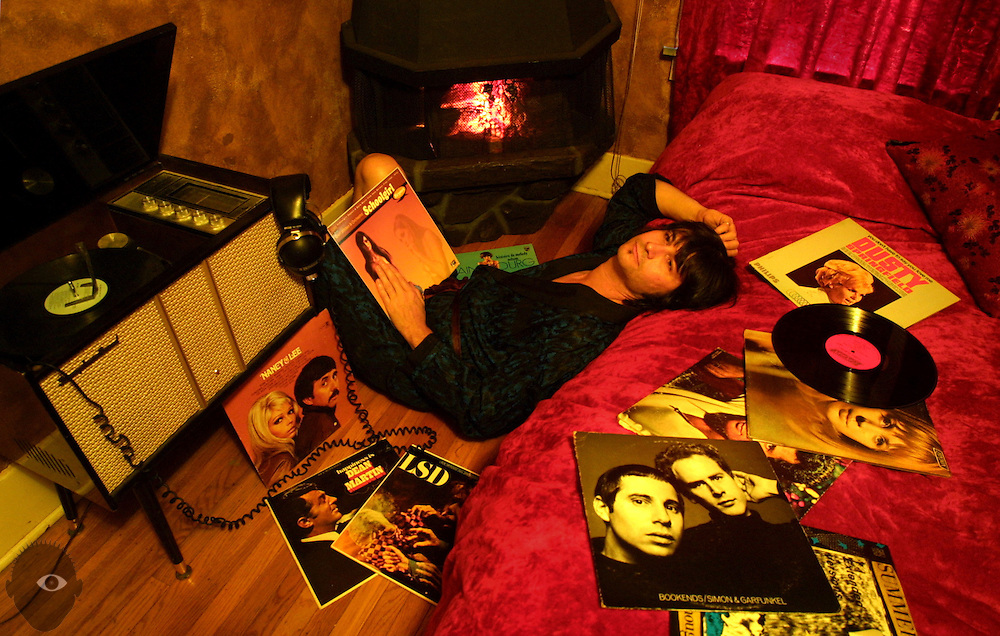 D.J. Gregarious listens to music while in his Portland bedroom, illuminated by an electric fireplace and yellow room lights.