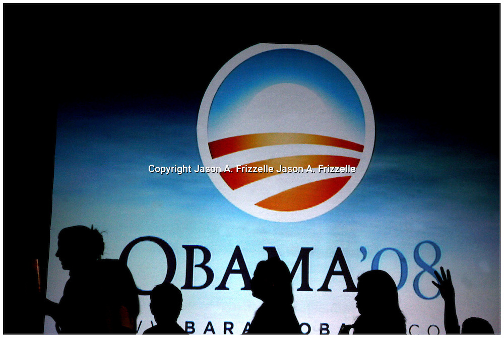 """Supporters of Barack Obama walk past a projection screen while finding seats Thursday at Minges Coliseum. (Jason A. Frizzelle) This collection of images represents more than a decade of work at newspapers and wire services throughout North Carolina. I now practice my style of story-telling photography for weddings community events as well as portrait sessions ranging from brides to local authors. After graduating from Randolph Community College I spent more than a decade documenting communities throughout Eastern North Carolina with a camera. My passion for capturing story-telling images has allowed me to witness everything from High School Football to Hurricanes and even Presidential visits.<br /> <br /> My award-winnng photography has been published internationally, appearing in publications such as The Atlanta Journal Constitution, The Los Angeles Times, USA Today, The Guardian of London, and Time Magazine.<br /> <br /> As a child I loved the writing of Ray Bradbury, who was often noted for """"tuning the ordinary into the extraordinary."""" That's the approach I take to every assignment, finding the priceless moments in everyday life. Weather I'm capturing a high school touchdown celebration or a bride's final minutes before saying """"I do,"""" I'm preserving an extraordinary memory.<br />             <br /> Whether I'm documenting a diverse community or capturing a couple's first dance, I'm photographing something extraordinary!"""