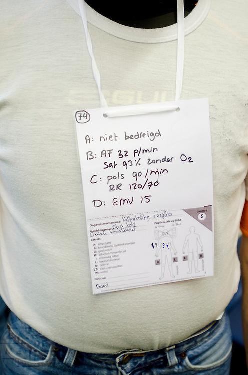 Een lotusslachtoffer draagt een kaart met zijn verwondingen. In het Calamiteitenhospitaal in Utrecht wordt een rampenoefening gehouden. De nadruk ligt op de contaminatie, door een gekantelde vrachtwagen zijn veel slachtoffers in aanraking gekomen met een chemische stof. Voor het eerst wordt er geoefend met een zogenaamde decontaminatietent. Als de tent bevalt, schaft het ziekenhuis zo'n tent aan. Bij de 'ramp' zijn 100 slachtoffers gevallen.<br /> <br /> An actor is carrying a card with his 'injuries'. In the Trauma and Emergency Hospital in Utrecht an calamity training was held. The emphasis is on the contamination by an overturned truck, many victims are contaminated by a chemical. For the first time a so-called decontamination tent was used. If the tent fulfills the expectations, a tent will be purchased. The 'calamity' caused 100 victims.