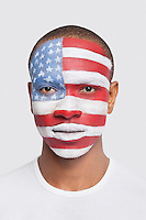 Portrait of young Hispanic man with North American flag painted on face against white background