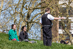 © Licensed to London News Pictures. 19/04/2020. London, UK. A policeman speaks to two members of the public with as Police patrol Primrose Hill enforcing lockdown rules on social distancing and exercise as Ministers urge councils to keep parks open to the public during lockdown. Photo credit: Alex Lentati/LNP