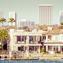 Newport Beach skyline vintage panorama picture with Newport Beach office buildings and waterfront homes along Newport Harbor. Newport Beach is a wealthy city in Orange County California. Panoramic ratio is 1:3. Photo has vintage retro 1950s tone.