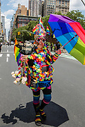 """New York, NY - 25 June 2017. New York City Heritage of Pride March filled Fifth Avenue for hours with groups from the LGBT community and it's supporters. A man in a costume covered in flowers with a sign that reads """"The Party's Here!"""""""